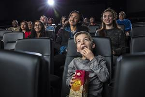 Boy eating popcorn in movie theater